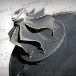 Uszkodzenie mechaniczne łopatek turbiny spowodowane uderzeniem twardego elementu znajdującego się w spalinach. Widoczne ubytki materiału w miejscach kontaktu łopatek ze strumieniem spalin opuszczających kolektor wydechowy silnika.